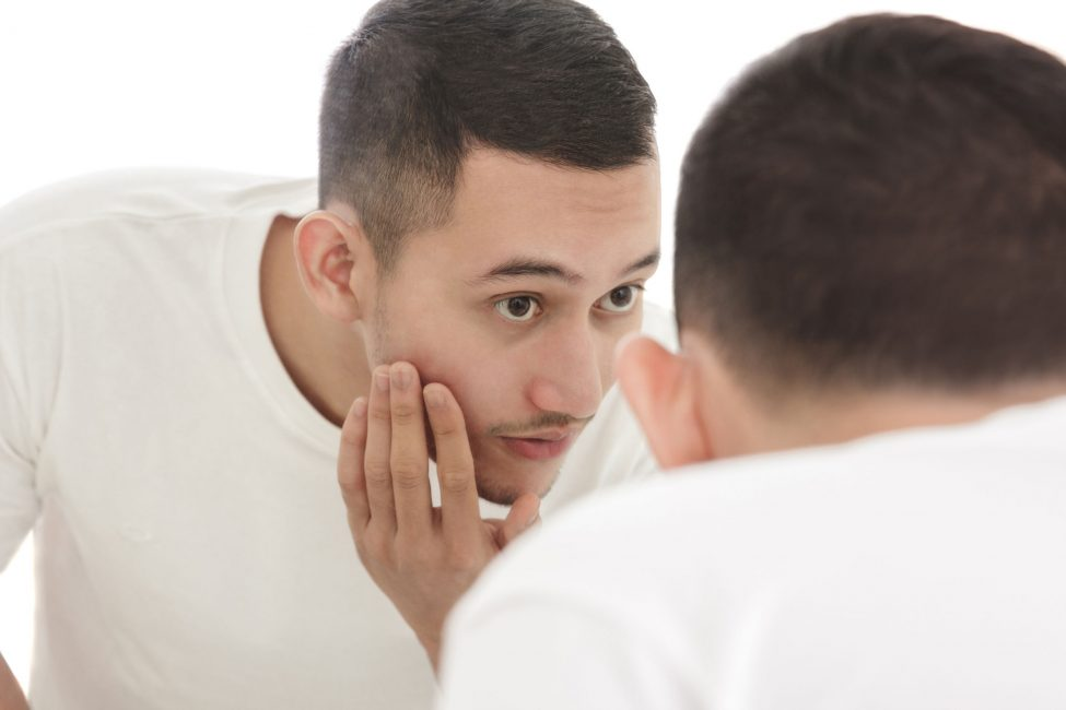 young man looking in mirror for acne