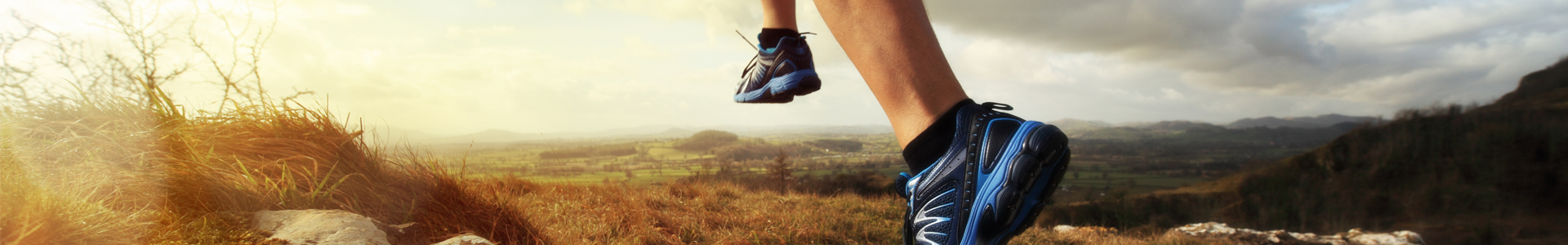 a runner's feet running up a mountain trail