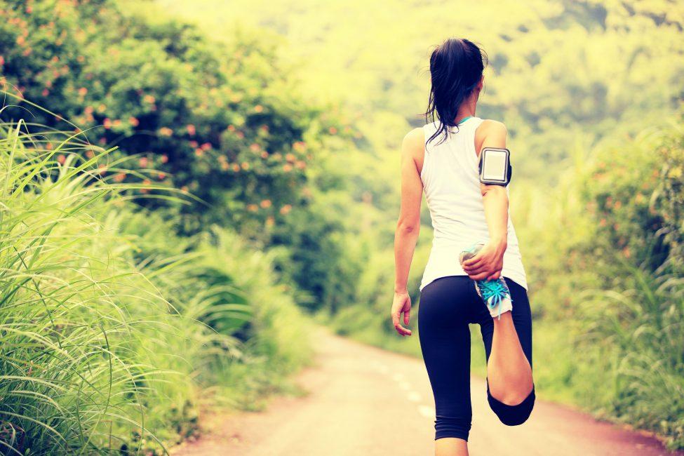 female runner stretching leg