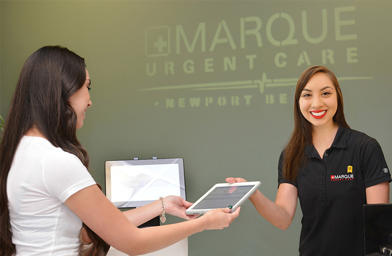 A receptionist at Marque Urgent Care helping a patient get signed in.