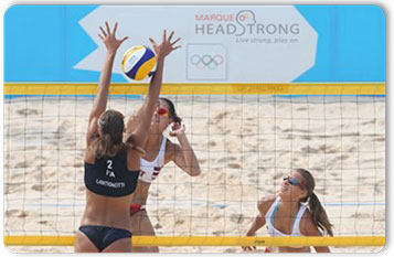 Female volleyball players playing a game on the beach