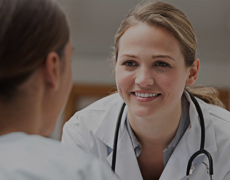 A female doctor smiling at a female patient. This is a banner image that represents the page on women's health.