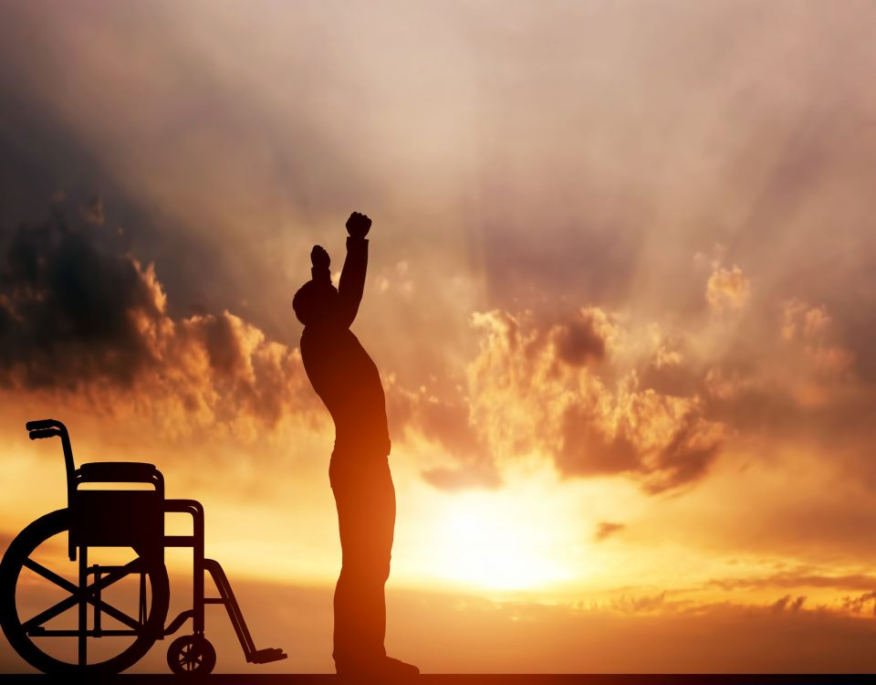 man standing up from wheelchair against the sunset