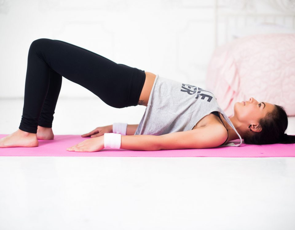 young woman exercising hips in yoga pose