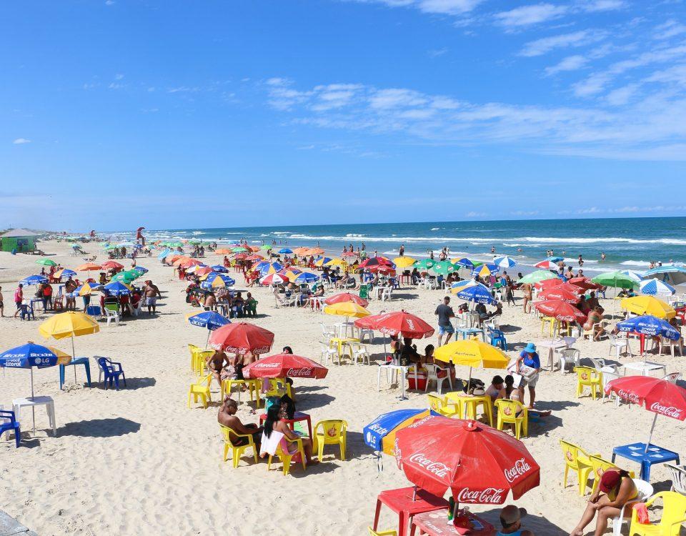 crowded public beach with umbrellas