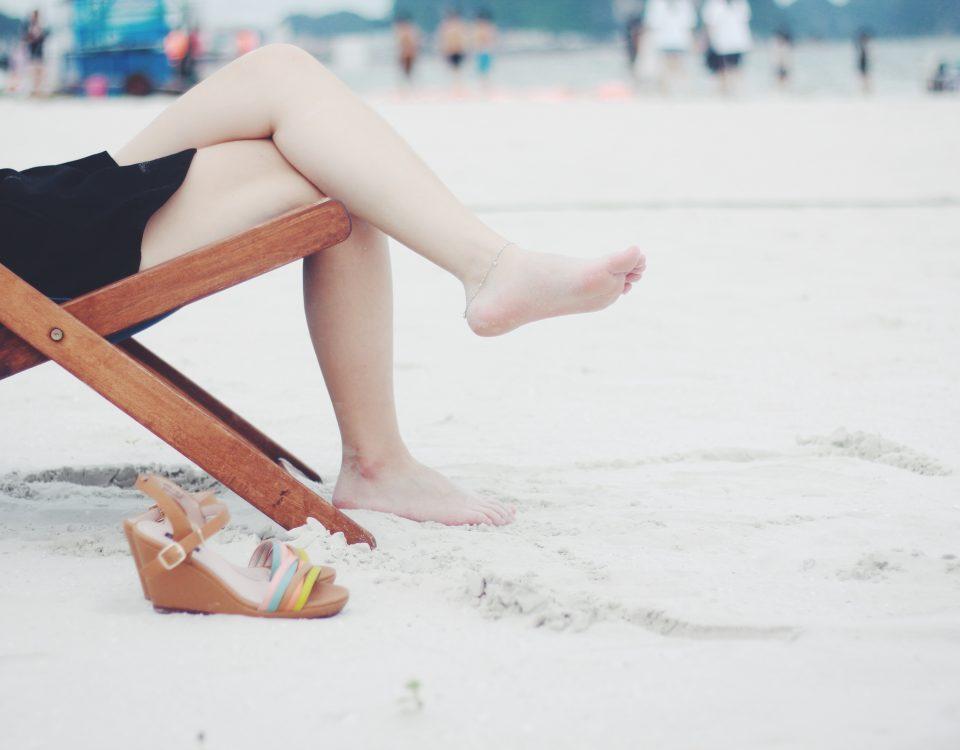woman's legs crossed on a beach