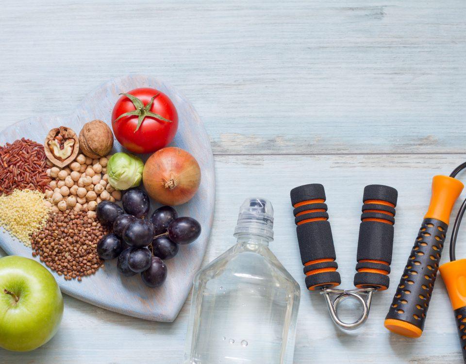 plate of fruits and grains next to a bottled water and jump rope