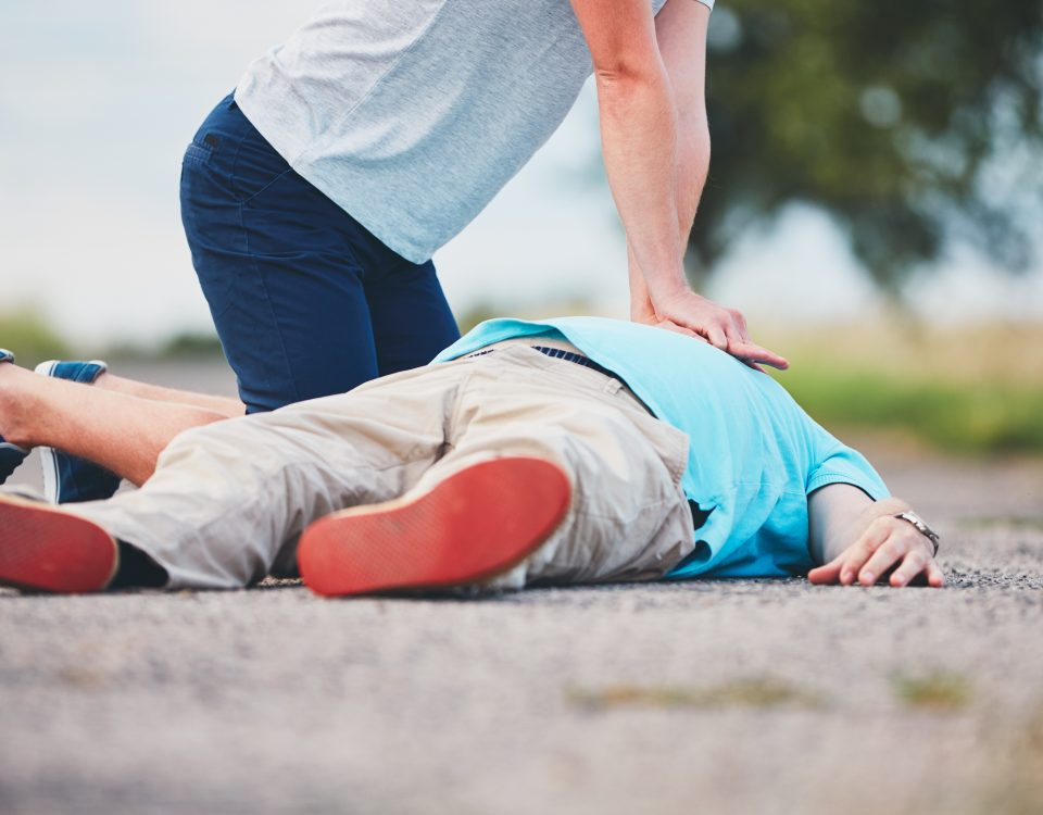 woman giving a man CPR on a rural road.